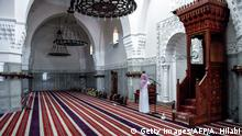 Imam Mohammed, muezzin of the Jaffali mosque in Saudi Arabia's Red Sea coastal city of Jeddah, announces the prayer call at the mosque which is closed due to a government decree as part of efforts to combat the COVID-19 coronavirus pandemic, during the Muslim holy month of Ramadan on April 28, 2020. (Photo by Amer HILABI / AFP) (Photo by AMER HILABI/AFP via Getty Images)