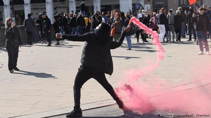 A protester dressed in black about to throw a smoke cartridge at police