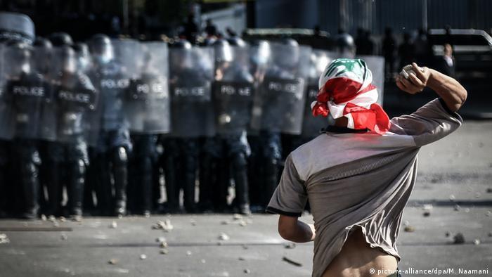 Foto de manifestante frente a policías en Líbano