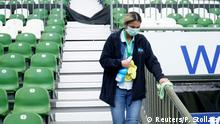 Soccer Football - Bundesliga - Werder Bremen v VfL Wolfsburg - Weser-Stadion, Bremen, Germany - June 7, 2020 A staff member wearing a protective face mask disinfects an area in the stands before the match, as play resumes behind closed doors following the outbreak of the coronavirus disease (COVID-19) Patrik Stollarz/Pool via REUTERS DFL regulations prohibit any use of photographs as image sequences and/or quasi-video
