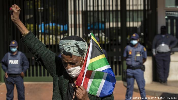 A woman holds a South African flag during a protest in Pretotia (picture-alliance/AP Photo/T. Hadebe)