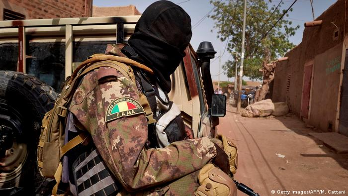 A Malian soldier sits on the back of a truck in Djenne
