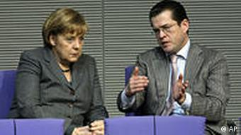 Angela Merkel with a skeptical face sitting next to Guttenberg