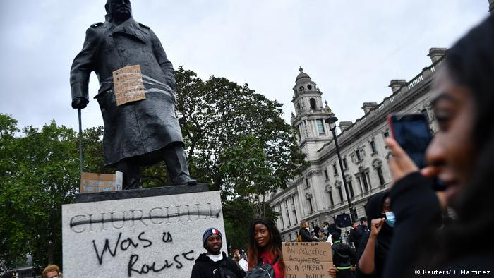 Demonstrators react in front of graffiti on a statue of Winston Churchill, where his name is crossed out, with the words 'was a racist'.