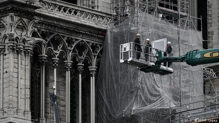 Restorers in a crane in front of the facade of Notre Dame Cathedral in Paris