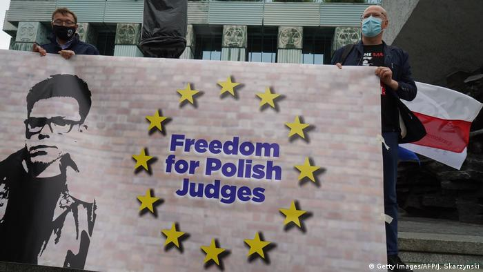 Protesters hold a sign saying Freedom for Polish Judges