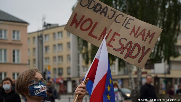 A protester wearing a mask waves a Polish flag outside the Supreme Court in Warsaw
