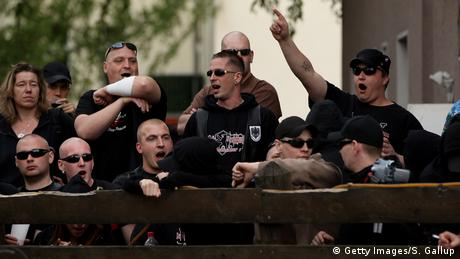 Men with shaved heads, dressed in black shouting outside a well-known hang-out for neo-Nazis in Berlin