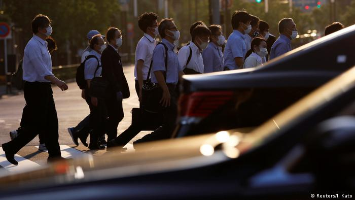 Office workers wearing protective face masks walk to head home at sunset amid the coronavirus disease (COVID-19) outbreak, in Tokyo, Japan