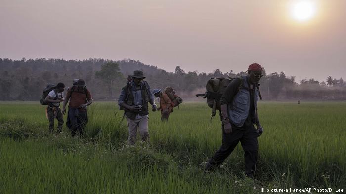 Film still 'Da 5 Bloods': 5 men wearing backpacks are wandering in a grassy field.