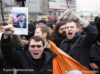 A protester holding a portrait of Moscow Mayor Yury Luzhkov takes part in an opposition rally in Moscow