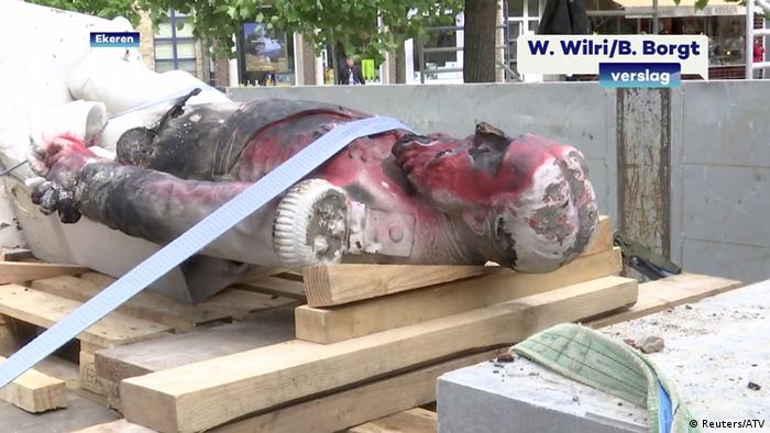 A damaged statue of former Belgian King Leopold II is seen being removed