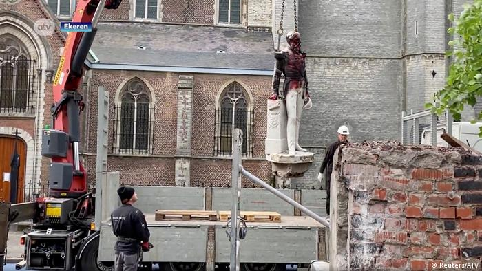 Tower crane lifts a staute of a figure, two men watch, church in the background (Reuters/ATV)