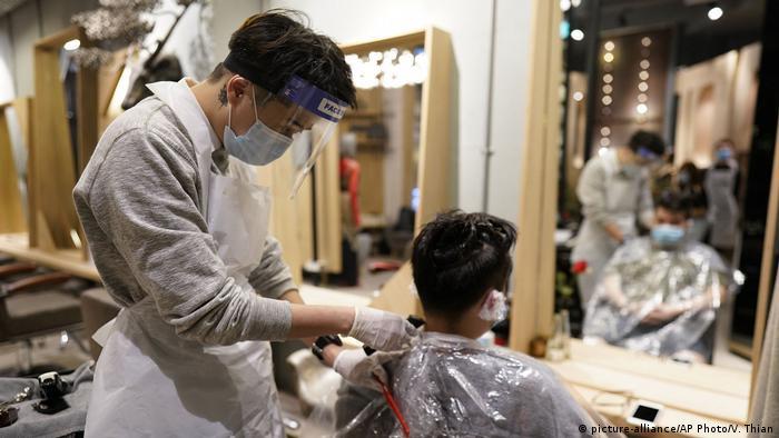 A barber cuts a man's hair in Kuala Lumpur