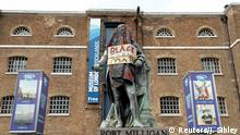 09.06.2020 *** A statue of Robert Milligan is seen covered with a blanket and a placard with a message in reference to the Black Lives Matter campaign outside the Museum of London Docklands near Canary Wharf, following the death of George Floyd who died in police custody in Minneapolis, London, Britain, June 9, 2020. REUTERS/John Sibley