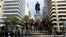 29.05.2020 *** Protesters stand on a statue of Henry Grady during a protest against the death in Minneapolis police custody of African-American man George Floyd, in Atlanta, Georgia, U.S. May 29, 2020. REUTERS/Dustin Chambers