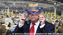 President Donald Trump looks through a face shield, in front of a poster of the manufacturing of the shields, while touring Ford Motor Co.'s Rawsonville Components Plant in Ypsilanti, Michigan on Thursday, May 21, 2020. (Daniel Mears/Detroit News via AP) |