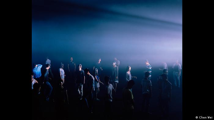 People moving around in the dark with a light from the side; photo by Chen Wei