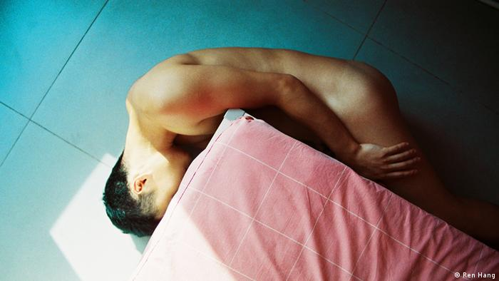 Naked man curled up into a ball around a pillow; photo by Ren Hang