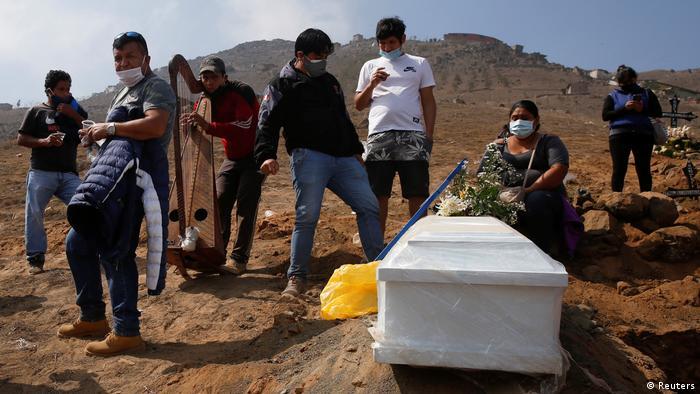 Familiares entierran a sus víctimas en un cementerio de Lima, Perú.