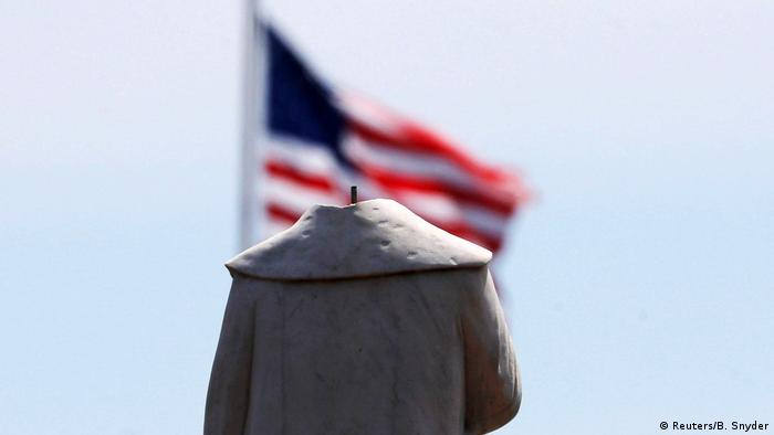Headless torso of a statue from behind, blurred US flag (Reuters/B. Snyder)