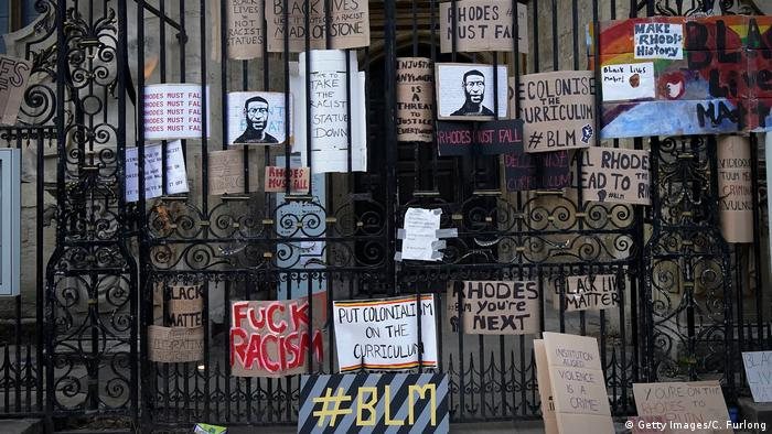 In this picture from June 9, 2020, protest prosters against racism and a statue of Cecil Rhodes hang on a gate at Oxford University