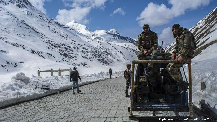 Indian army trooper stands guards atop his vehicle the snow-cleared Srinagar-Leh highway