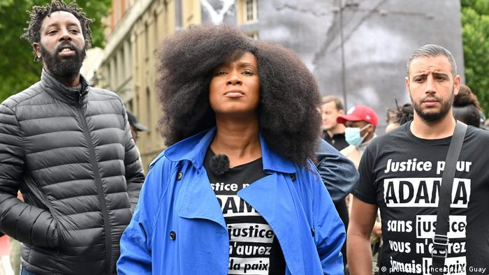 Adama Traoré's sister Assa Traoré backed by two male protesters wearing a bright blue coat