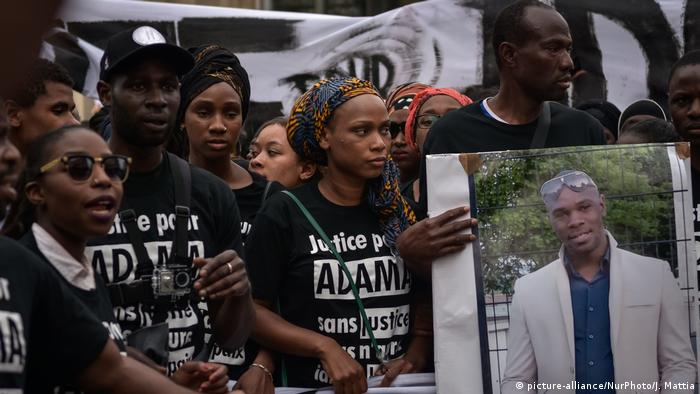 Protesters hold a placard of Adama Traoré and wearing t-shirts reading justice for Adama.