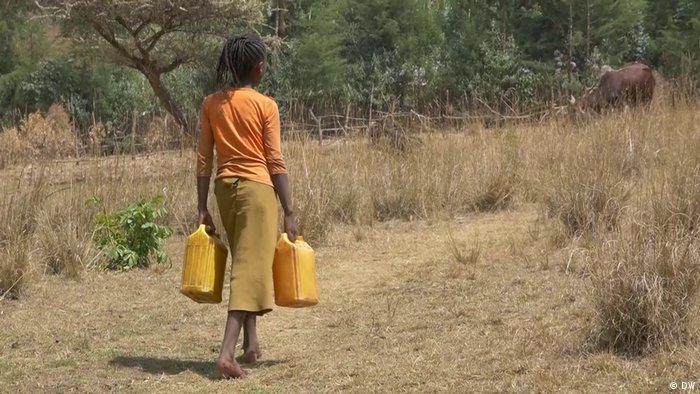 A woman carrying two water canisters walks through a dry landscape