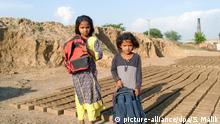 Die siebenjährige Manal und die fünfjährige Laiba stehen am 27.04.2016 auf dem Gelände einer Ziegelbrennerei in einem Vorort von Islamabad, Provinz Punjab (Pakistan). Ein neues Gesetz verbietet Kinderarbeit in pakistanischen Ziegelbrennereien. Trotzdem arbeiten die beiden Kinder nach der Schule in der Brennerei. Foto: Sajjad Malik/dpa (zu dpa «Pakistan geht gegen Kinderarbeit in Ziegelbrennereien vor» vom 09.06.2016) +++(c) dpa - Bildfunk+++ | Verwendung weltweit