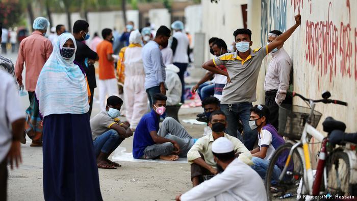 People wait outside a coronavirus testing center in Dhaka