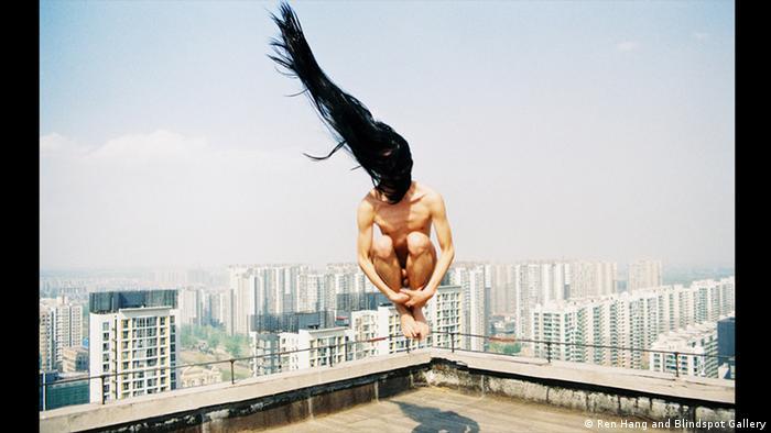 Ein nackter Mann im Sprung, dessen lange Haare durch den Wind nach oben fliegen. Foto von Ren Hang (Ren Hang and Blindspot Gallery)
