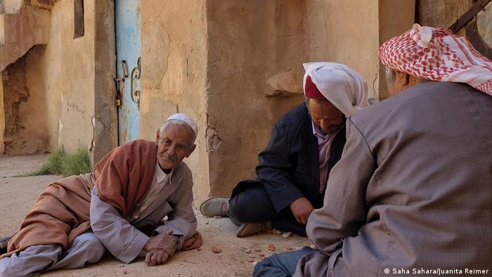 Three older men sit on the ground playing a game with stones