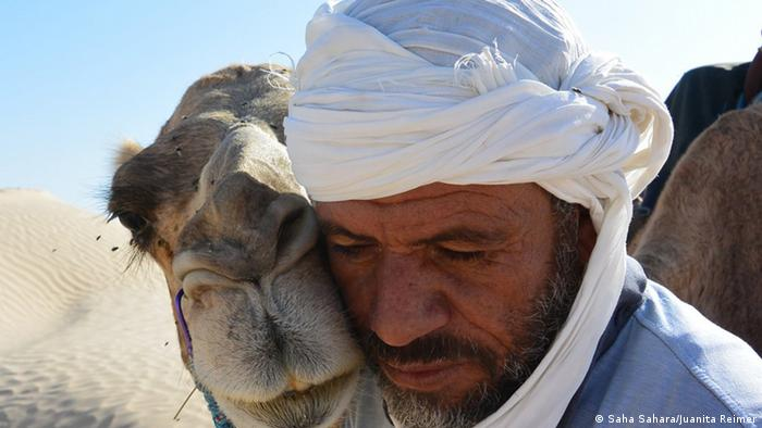 A tour guide in the desert with his camel, which is pressing its face up against his