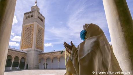 Жительница Туниса в защитной маске на фоне мечети