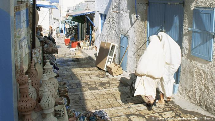 A largely empty narrow street with steps and ornaments lining its left hand side