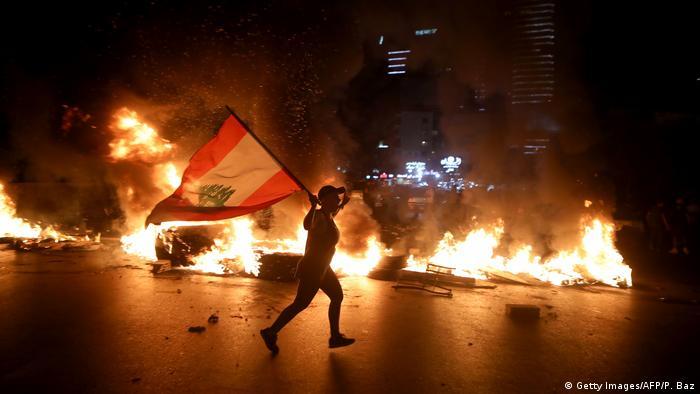 متظاهر في بيروت يحمل العلم اللبناني