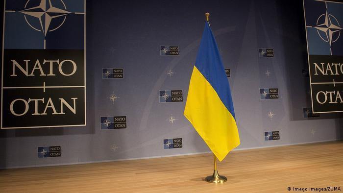 Флажок с национальными цветами Украины на фоне символики НАТО