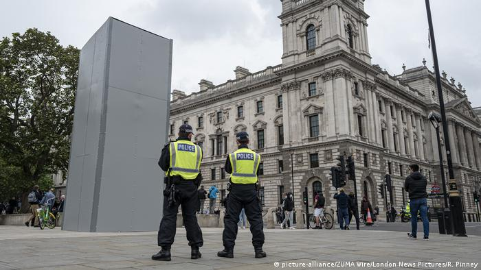 Two police officers stand in front of the Winston Churchill statue in Parliament Square, which has been temporarily boxed in.