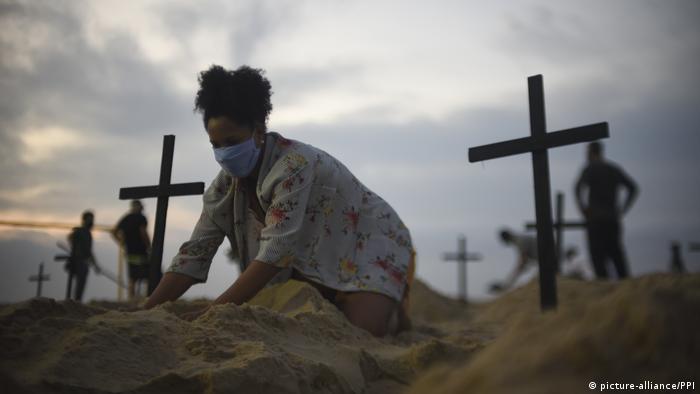 Manifestante simula túmulos na areia em praia do Rio de Janeiro, em protesto contra inação do governo na pandemia