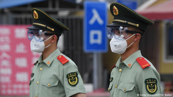 Two police officers in Beijing wearing face masks and protective goggles.