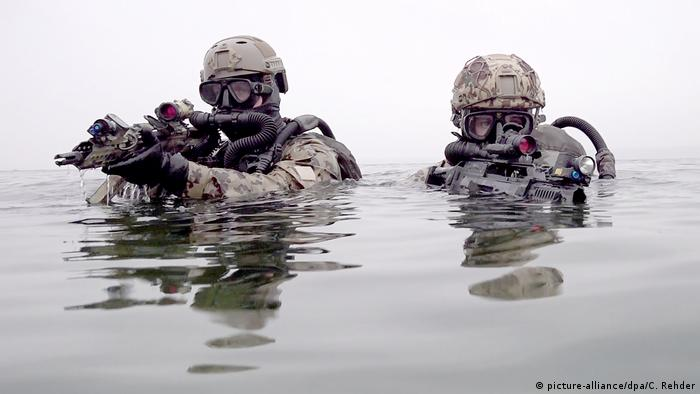 Two KSM fighters swimming with their weapons