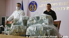 Ukraine's Anti-Corruption Prosecutor Nazar Kholodnytsky, left, and National Anti-Corruption Bureau chief Artem Sytnik at a pile of USD 6 million in plastic bags during a briefing in an anti-corruption prosecutor's office in Kyiv, Ukraine, Saturday, June 13, 2020. Ukrainian authorities say they have intercepted a USD 6 million bribe attempt at dropping a criminal investigation against the head of the Burisma natural gas company where former US Vice President Joe Biden's son once held a board seat. (AP Photo/Efrem Lukatsky) |