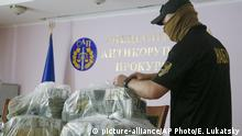 A police officer holds USD 6 million at a briefing in an anti-corruption prosecutor's office in Kyiv, Ukraine, Saturday, June 13, 2020. Ukrainian authorities say they have intercepted a $6 million bribe attempt at dropping a criminal investigation against the head of the Burisma natural gas company where former US Vice President Joe Biden's son once held a board seat. (AP Photo/Efrem Lukatsky) |