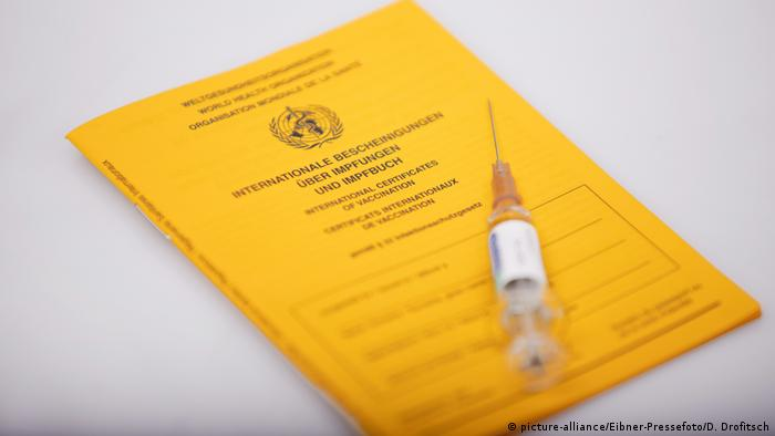 Vaccination syringe and vaccine record (picture-alliance/Eibner-Pressefoto/D. Drofitsch)