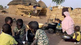 A Nigerien woman cooks millet paste as children eat breakfast from a shared bowl