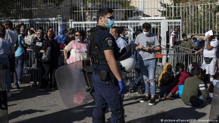 Asylum-seekers wait in line to file asylum applications at an Athenian administrative bureau