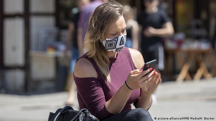 Würzburg | Frau mit Mundschutz guckt auf Ihr Handy