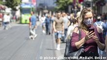 W?rzburg, 13.06.2020, Coronavirus: Was kann die Corona-Warn-App Bild: Eine junge Frau mit Mundschutz schaut in der City auf Ihr Handy. Wird dies mit der Corona-Warn-App zur Normalitaet F?r den Weg aus der Corona-Krise in die Normalitaet hoffen viel Menschen auch auf die seit Monaten angekuendigte Corona-Warn-App. Sie soll dabei helfen, die Infektionsketten fruehzeitig zu erkennen und zu durchbrechen. | Verwendung weltweit